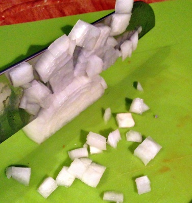 Agora, é só cortar, de cima para baixo, com a lâmina paralela às extremidades da cebola.