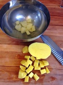 Cortando as batatas em cubinhos e jogando imediatamente na água fria